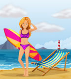 A girl at the beach with a colourful surfing board Royalty Free Stock Photo