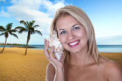 Girl on the beach with conch Royalty Free Stock Photo
