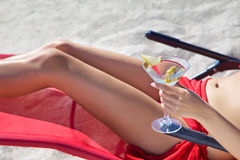 Girl  the beach in  deck chair with a glass. Girl  the beach in deck chair with  glass of martini Stock Photos