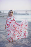 Girl on the beach. In developing long dress royalty free stock photography