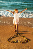 Girl at the beach drawing heart on a sand Royalty Free Stock Image