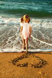 Girl at the beach drawing heart on a sand Stock Photo