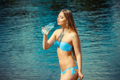 Girl on the beach drinking water. Stock Images