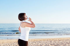 The girl on the beach after exercise drink, water. Stock Photos
