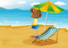 A girl at the beach with a foldable chair and an umbrella Stock Photo