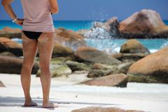 Girl on the beach in front of the Seychelles white sail boat sails on the blue sea Royalty Free Stock Photos