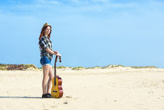 Girl on beach with guitar Stock Photography