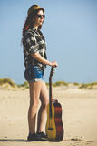 Girl on beach with guitar Stock Images