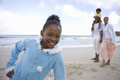 Girl (7-9) on beach with hand on hip, smiling, portrait, family in background Royalty Free Stock Photo