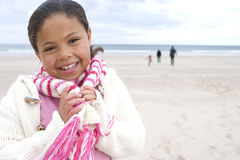 Girl (7-9) on beach, hands on scarf, family in background, smiling, portrait Stock Photography