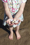 Girl On Beach Holding Handful Of Seashells Stock Photo