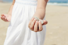 Girl on the beach holding stones Stock Image