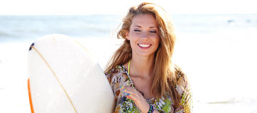 Girl on the beach holding a surfboard Royalty Free Stock Photos
