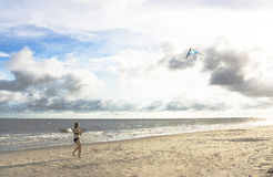 Girl on the beach with kite. Horizontal image. girl in the beach suit holding the kite that flown in the sky. the sky has dark cloud and some places just blue Stock Photo