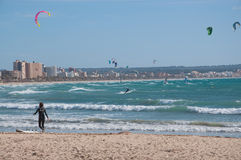 Girl on beach with kite surfers Royalty Free Stock Photos
