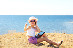 Girl on the beach with laptop and phone Stock Photos