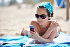 Girl on the beach listening music Royalty Free Stock Photography