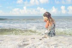 Girl on the beach listening seashell Stock Photos