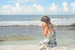 Girl on the beach listening seashell Royalty Free Stock Images