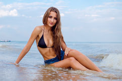 Girl on the beach. Long hair girl with jeans shorts sitting on the beach Stock Photos