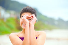 Girl on beach looking through hands made in heart shape royalty free stock images