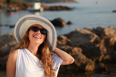 Girl on the beach looking the sunset. Blondy girl with sunglasses and hat lovely the sun on the beach Stock Photos