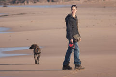 Girl on beach with lurcher dog. The girl has spotted the camera for a smile but the dog's not interested Royalty Free Stock Photo