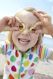 Girl On Beach Making Glasses From Seashells Stock Photography