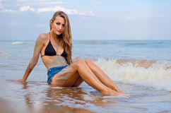Girl on the beach. Girl with mud on her skin sitting on the beach royalty free stock image