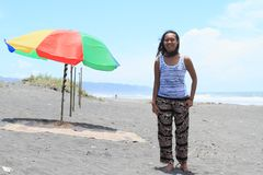 Girl on beach by parasol. Young Papuan woman - smiling pretty girl standing on sandy beach with dark sand by red, green and yellow parasol by sea stock image