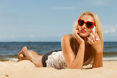Girl on beach with phone. Royalty Free Stock Photos