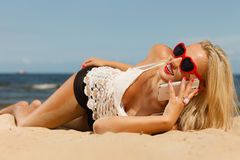 Girl on beach with phone. Royalty Free Stock Image