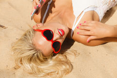 Girl on beach with phone. Young girl lying on beach with sunglasses using cellular phone. Communication and internet concept Royalty Free Stock Images
