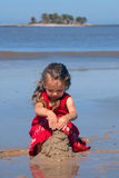 Girl on the beach playing with sand Royalty Free Stock Photo