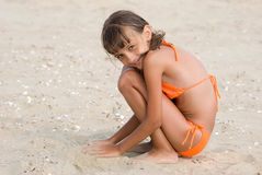 The girl on a beach. The girl plays in sand on a beach Royalty Free Stock Images