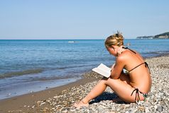 Girl on beach reading book Stock Photography