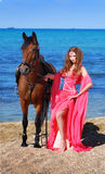 The girl on beach in red dress. Nearby costs horse Royalty Free Stock Photography