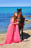 The girl on beach in red dress. Nearby costs horse Stock Photos