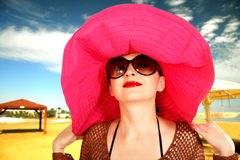 Girl on the beach in a red hat, a large glasses Stock Image