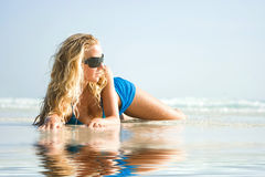 Girl on beach with reflection in water Royalty Free Stock Photos