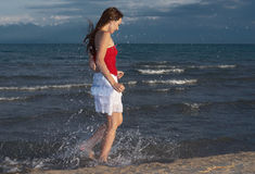 Girl on a beach runs. Girl runs on beach does spatter Royalty Free Stock Image