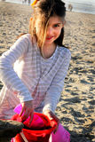 Girl at Beach with Sand Toys. A cute little 9 year old girl with dark messy hair playing in the sand at the beach with sand toys. Shallow depth of field Royalty Free Stock Photos