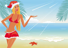 Girl on the beach in santa's hat Stock Photo