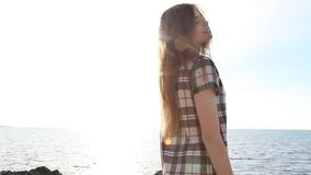 Girl on the beach by the sea waves wind. Sun stock video footage