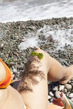 The girl on the beach with seaweed on a leg Stock Image