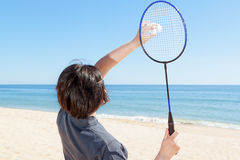 The girl on the beach serves playing badminton. Royalty Free Stock Images