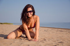 Girl on the beach. Smiling girl with black glasses sitting on the beach Royalty Free Stock Photography