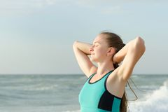 The girl on the beach standing with eyes closed and hands behind. Girl on the beach standing with eyes closed and hands behind head. Morning sun royalty free stock image