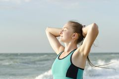 The girl on the beach standing with eyes closed and hands behind. Girl on the beach standing with eyes closed and hands behind head. Morning sun royalty free stock images