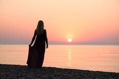 Girl on the beach at sunrise Royalty Free Stock Image